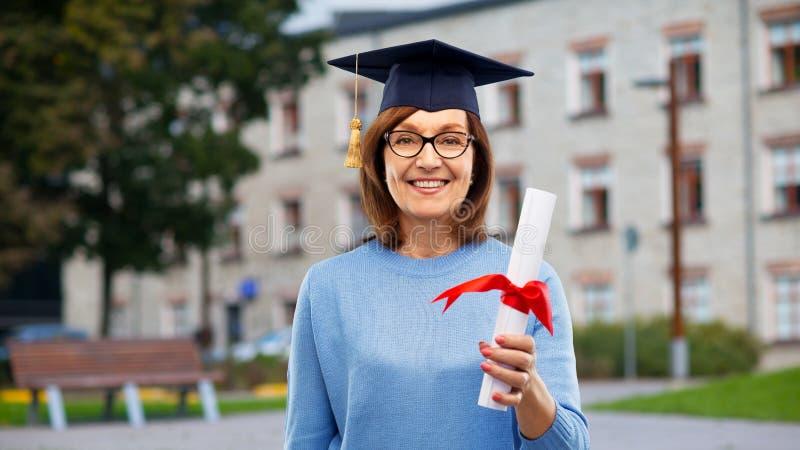 Mujer mayor feliz del estudiante de tercer ciclo con el diploma fotos de archivo