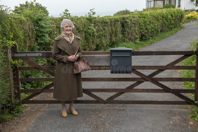Mujer mayor feliz en la puerta de jardín fotos de archivo libres de regalías