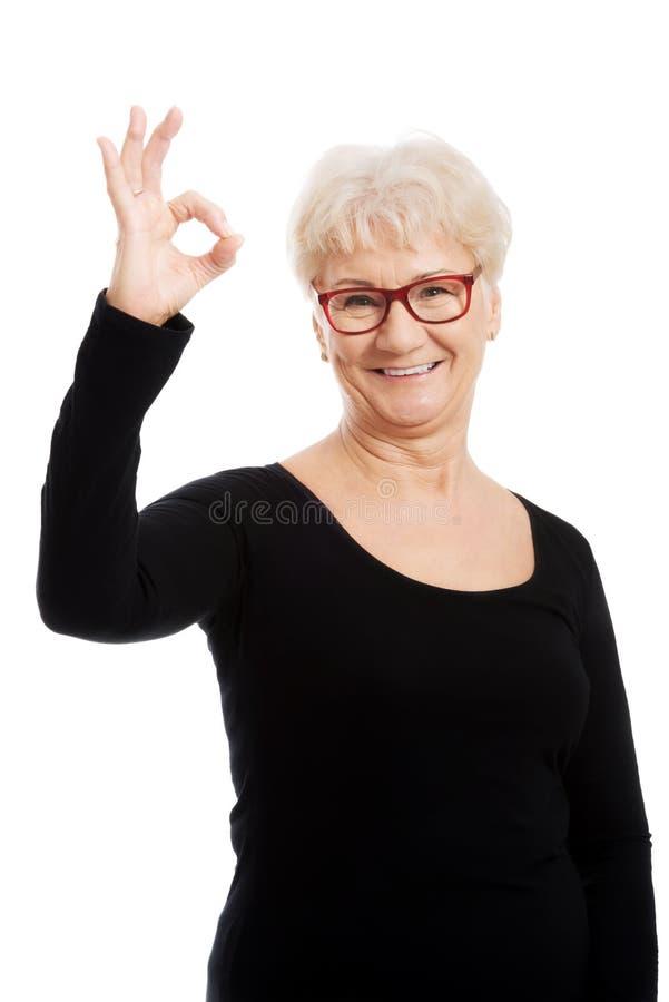 Mujer mayor feliz en los vidrios del ojo que muestran MUY BIEN. fotos de archivo libres de regalías