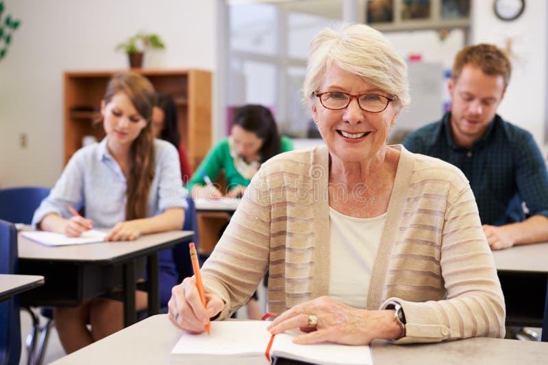 Mujer mayor feliz en una clase de la enseñanza para adultos que mira a la cámara foto de archivo libre de regalías