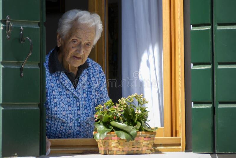 Mujer mayor feliz no identificada que mira fuera de la ventana de su casa fotografía de archivo libre de regalías