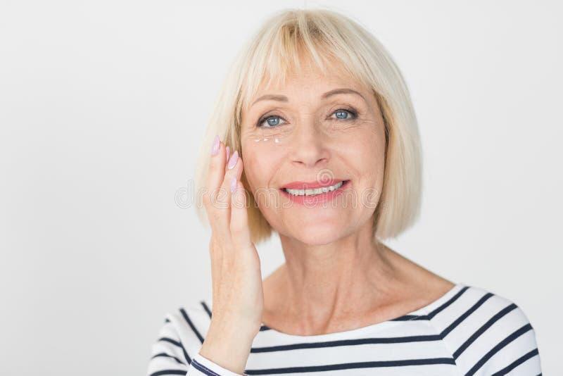 Mujer mayor feliz que aplica la crema antiarrugas del ojo foto de archivo