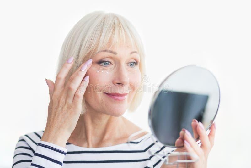 Mujer mayor feliz que aplica la crema antiarrugas del ojo fotografía de archivo
