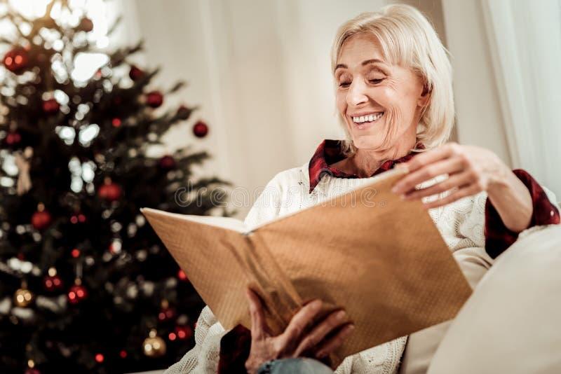 Mujer mayor feliz que celebra un libro y una sonrisa imágenes de archivo libres de regalías