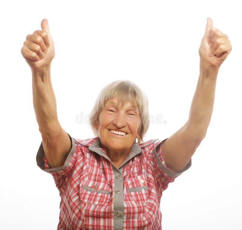 Mujer mayor feliz que da dos pulgares para arriba como muestra de la aprobación imágenes de archivo libres de regalías