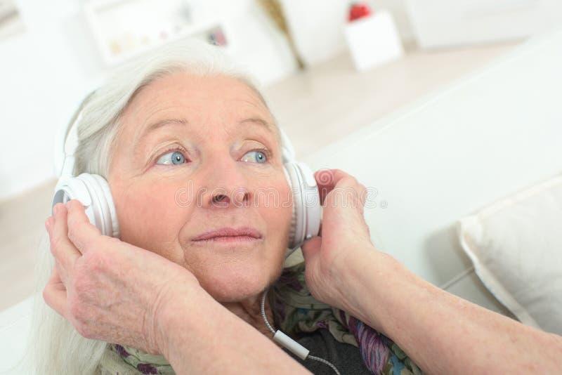 Mujer mayor feliz que disfruta de m?sica con el auricular en casa imagenes de archivo
