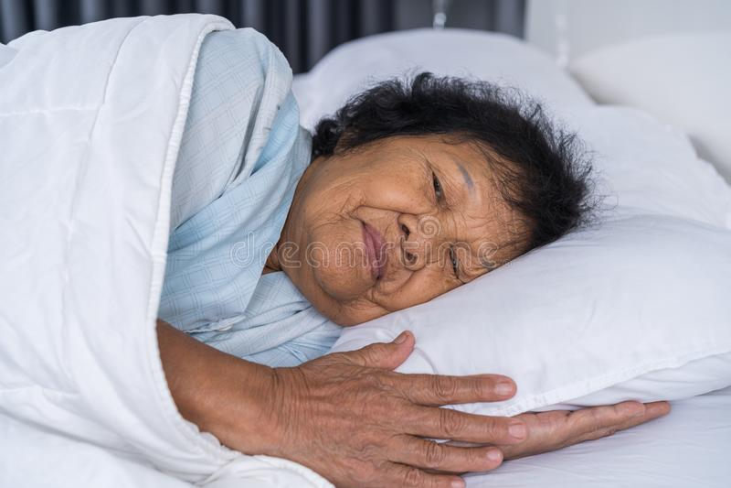 Mujer mayor feliz que duerme en cama foto de archivo