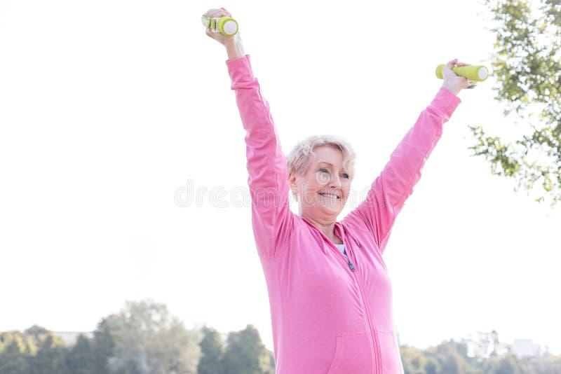 Mujer mayor feliz que ejercita con pesas de gimnasia en parque imagen de archivo