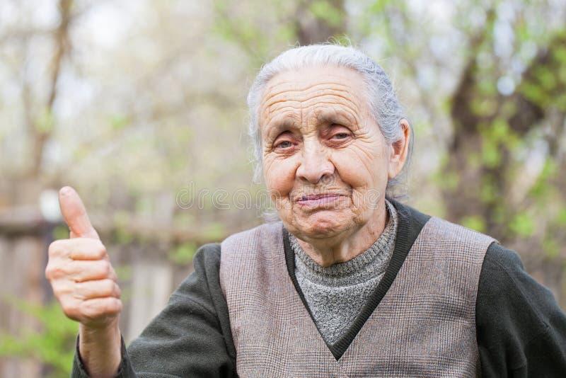 Mujer mayor feliz que muestra el pulgar encima de al aire libre imagenes de archivo