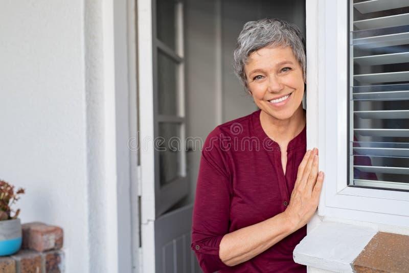 Mujer mayor feliz que se inclina en la puerta imagenes de archivo