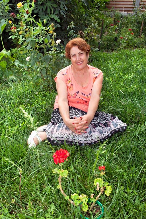 Mujer mayor feliz que se sienta en la hierba imagen de archivo libre de regalías
