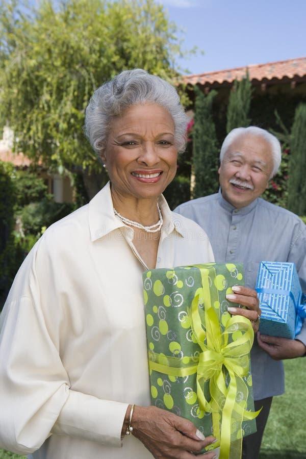 Mujer mayor feliz que sostiene el regalo foto de archivo libre de regalías