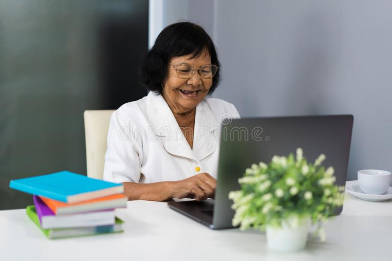 Mujer mayor feliz que trabaja en el ordenador portátil fotografía de archivo libre de regalías