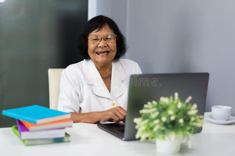 Mujer mayor feliz que trabaja en el ordenador portátil imagenes de archivo