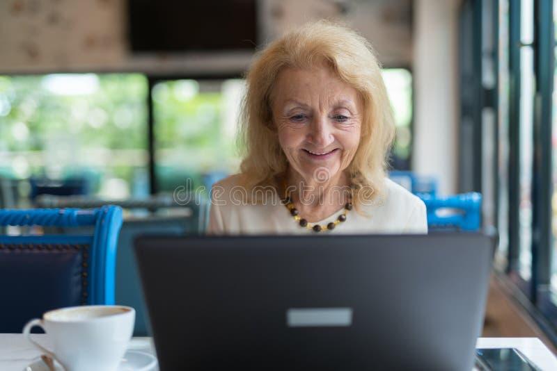 Mujer mayor feliz que usa el ordenador portátil imagenes de archivo