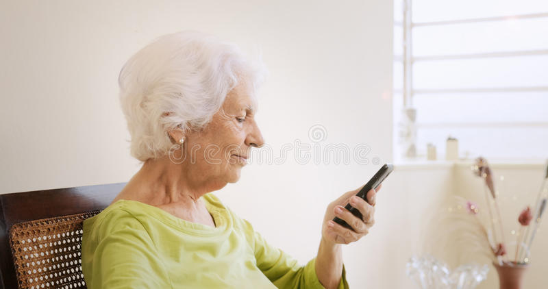 Mujer mayor feliz que usa el teléfono móvil para el ocio imagen de archivo