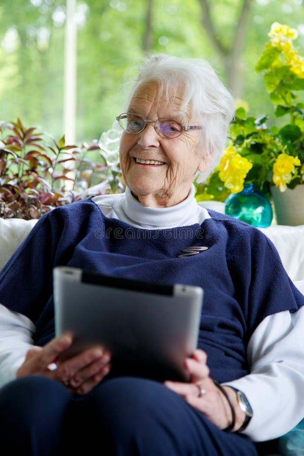Mujer mayor feliz que usa una tableta que mira la cámara y la risa imagen de archivo libre de regalías