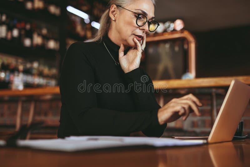 Mujer mayor hermosa del freelancer que usa el ordenador portátil en el café foto de archivo