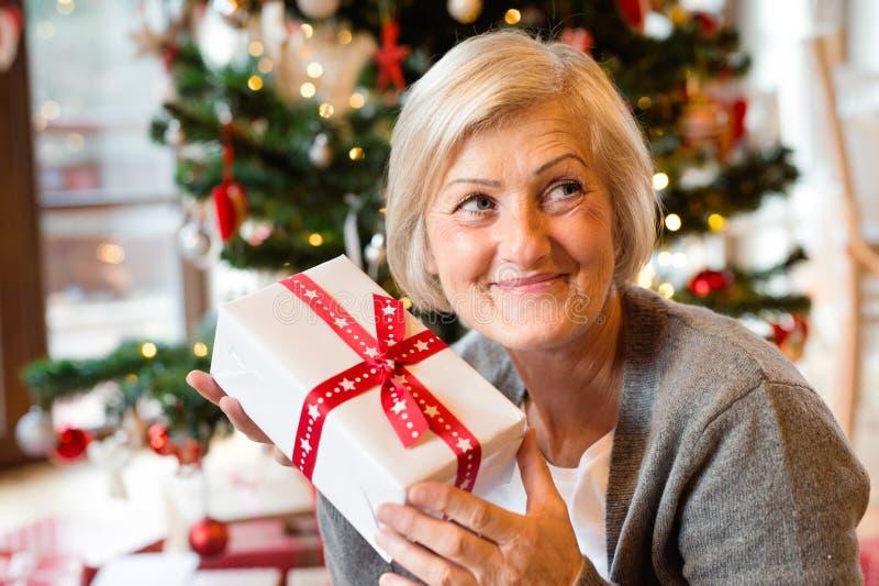 Mujer mayor hermosa delante del árbol de navidad con el presente foto de archivo libre de regalías
