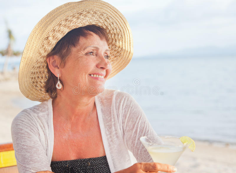 Mujer mayor hermosa en un sombrero con un cóctel a disposición Verano fotografía de archivo