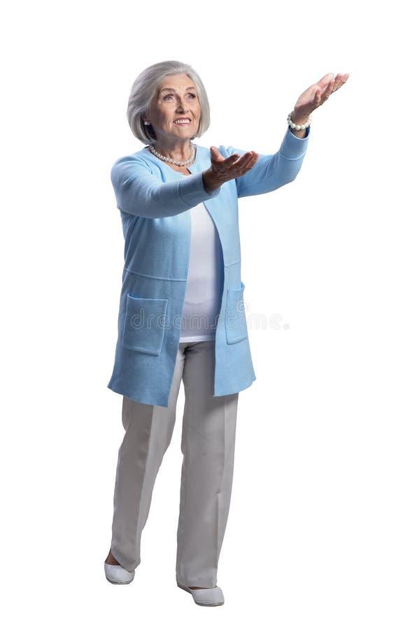 Mujer mayor hermosa feliz que presenta en el fondo blanco imagen de archivo libre de regalías