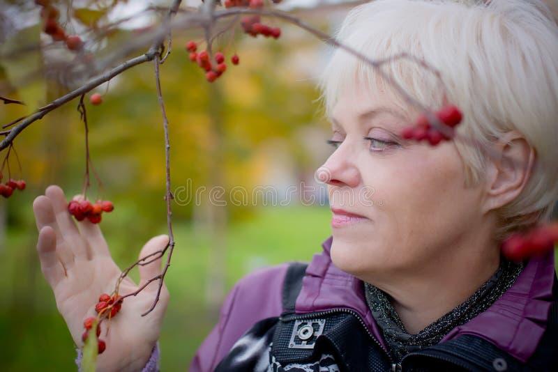 Mujer mayor hermosa que se relaja en el parque de la caída imagen de archivo