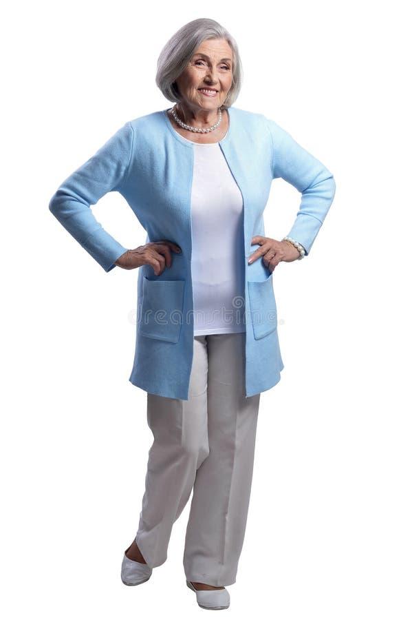 Mujer mayor hermosa sonriente que presenta en el fondo blanco fotos de archivo