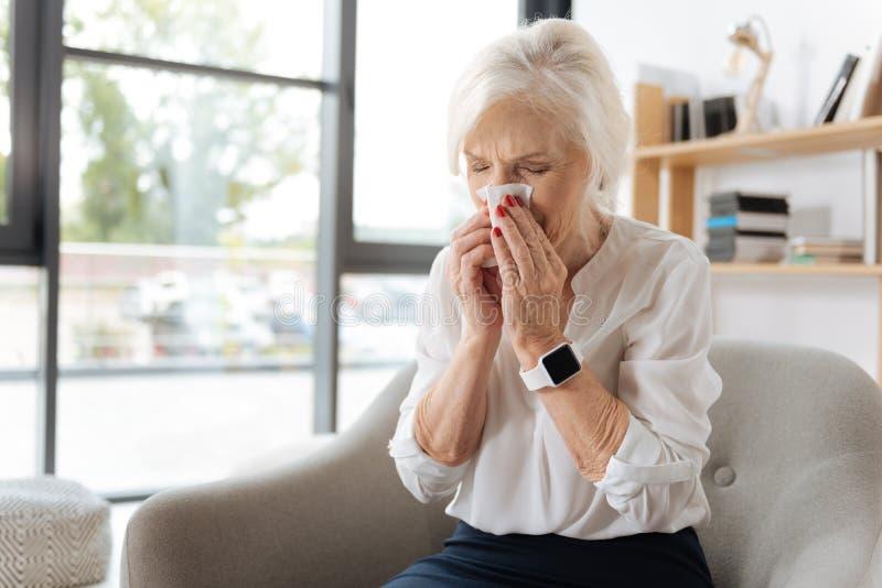 Mujer mayor infeliz que estornuda foto de archivo libre de regalías