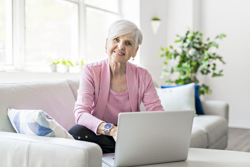 Mujer mayor jubilada que se sienta en casa usando su ordenador portátil fotos de archivo