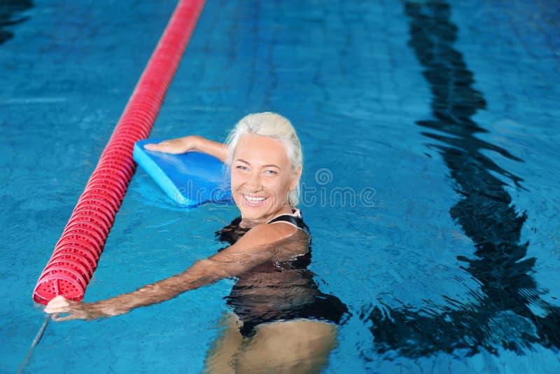 Mujer mayor juguetona en piscina interior foto de archivo