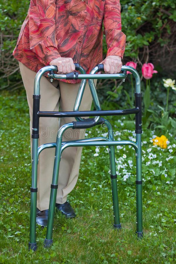 Mujer mayor lanzada en el caminante plegable fotos de archivo