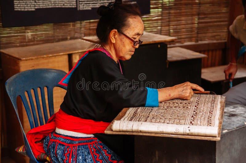 Mujer mayor laosiana hacer la pintura de la tela del batik imagenes de archivo