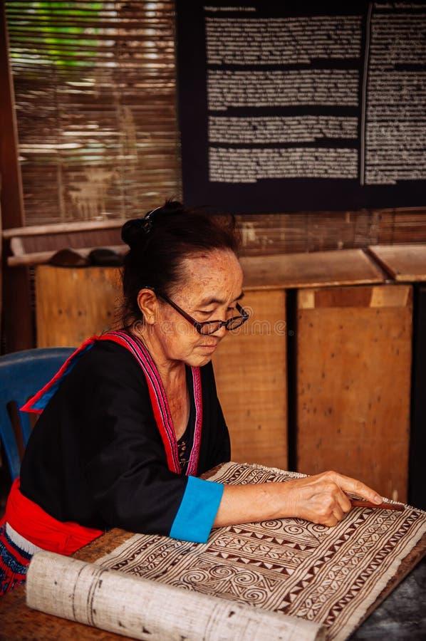 Mujer mayor laosiana hacer la pintura de la tela del batik foto de archivo