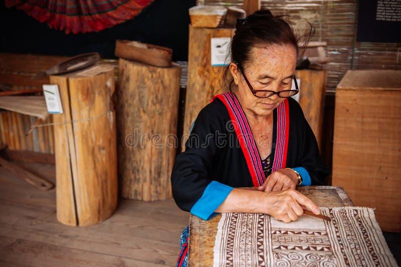 Mujer mayor laosiana hacer la pintura de la tela del batik fotografía de archivo