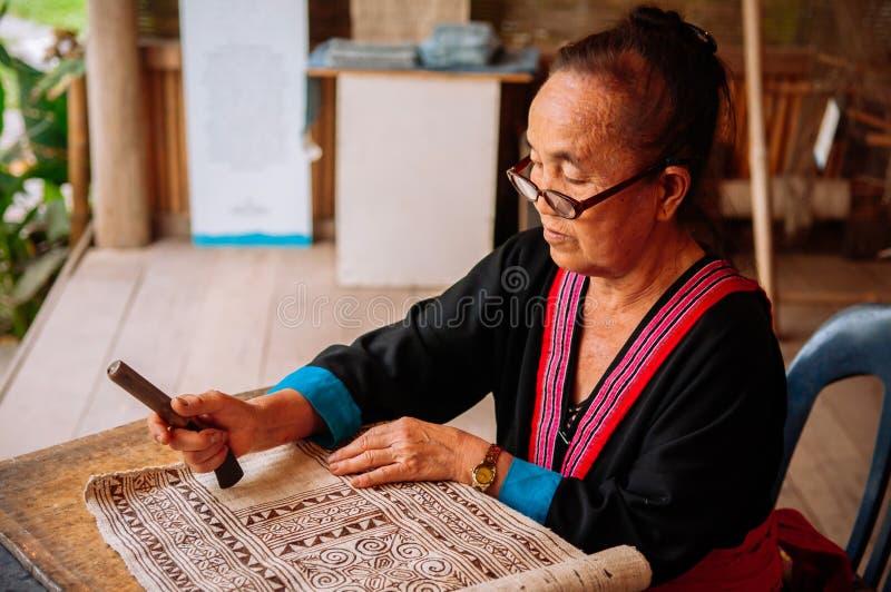 Mujer mayor laosiana hacer la pintura de la tela del batik imagen de archivo