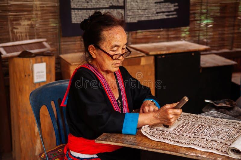 Mujer mayor laosiana hacer la pintura de la tela del batik imágenes de archivo libres de regalías