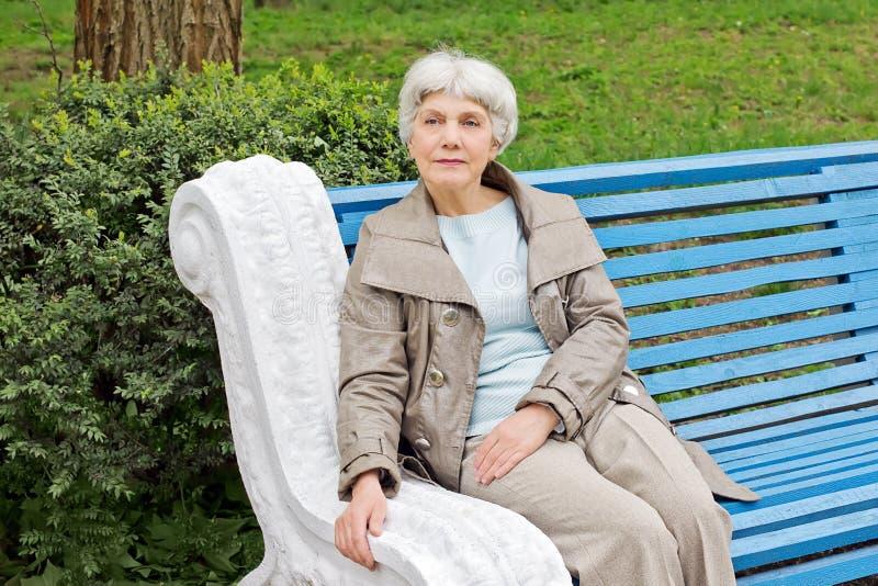 Mujer mayor linda hermosa que se sienta en azul del banco de parque fotos de archivo