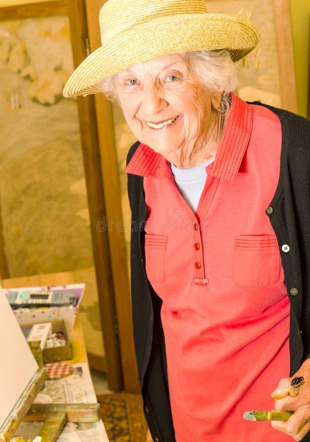 Mujer mayor, llevando un sombrero del sol, pintando en su caballete fotografía de archivo libre de regalías
