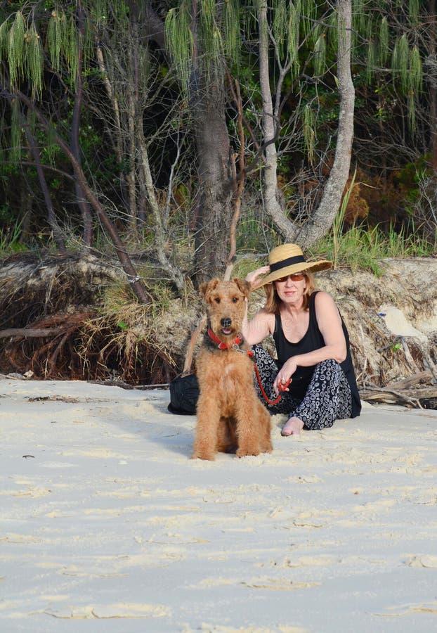 Mujer mayor madura de la voga elegante el día de fiesta de la playa del verano con el perro casero foto de archivo