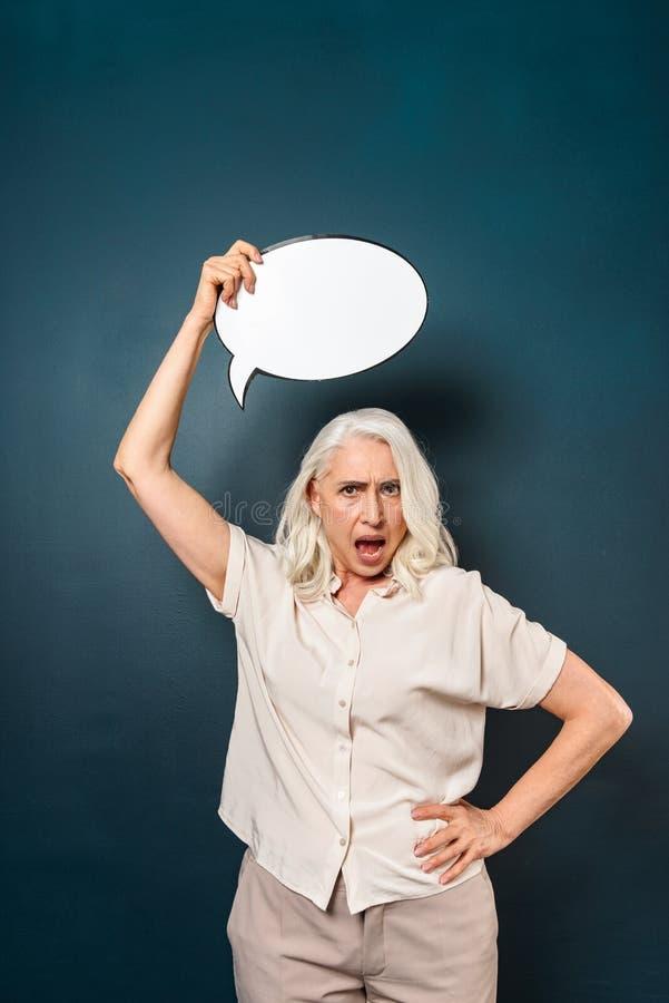 Mujer mayor madura descontentada que lleva a cabo la burbuja del discurso fotos de archivo