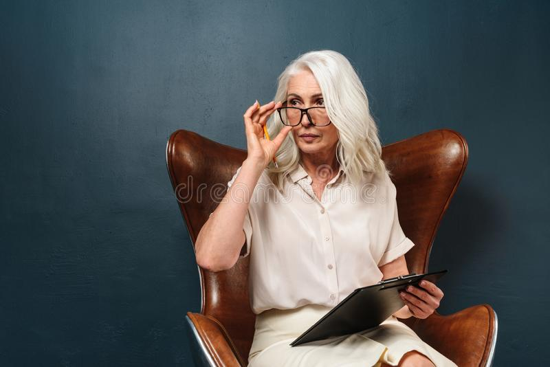 Mujer mayor madura seria que sostiene el tablero con los documentos que escriben notas foto de archivo libre de regalías