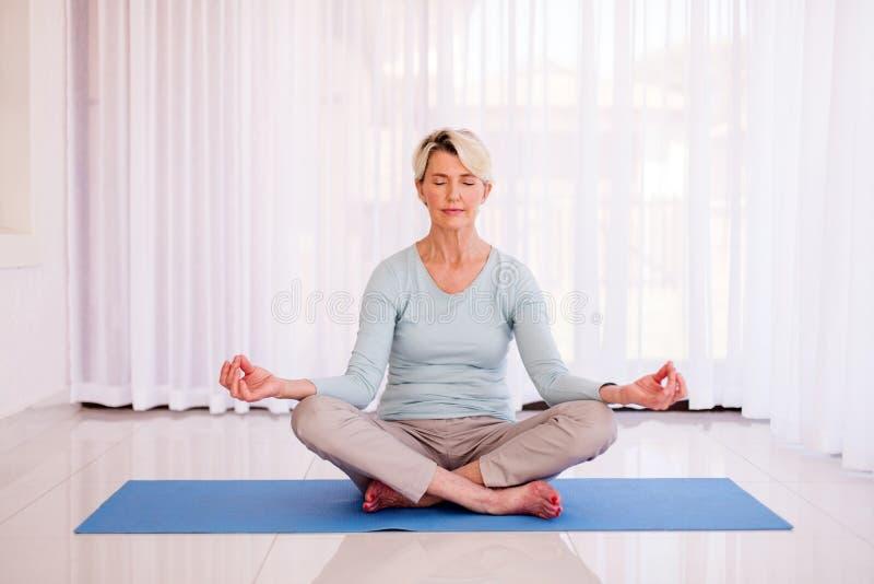 Mujer mayor meditating fotografía de archivo