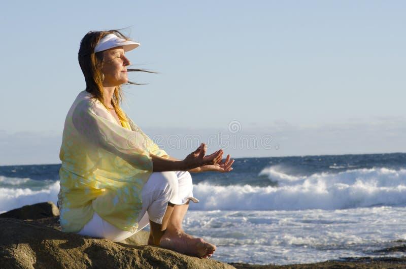 Mujer mayor meditating en el océano imágenes de archivo libres de regalías
