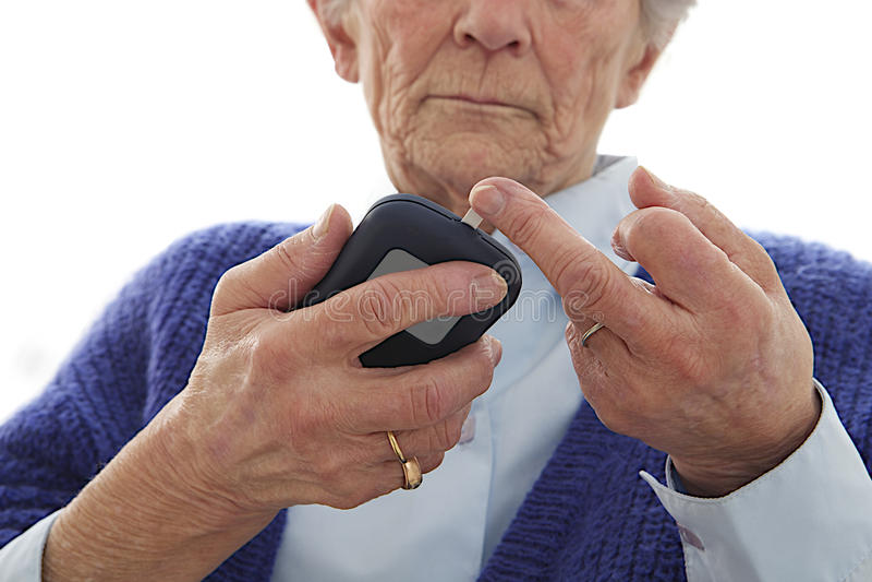 Mujer mayor mesuring el nivel suggar en sangre foto de archivo libre de regalías