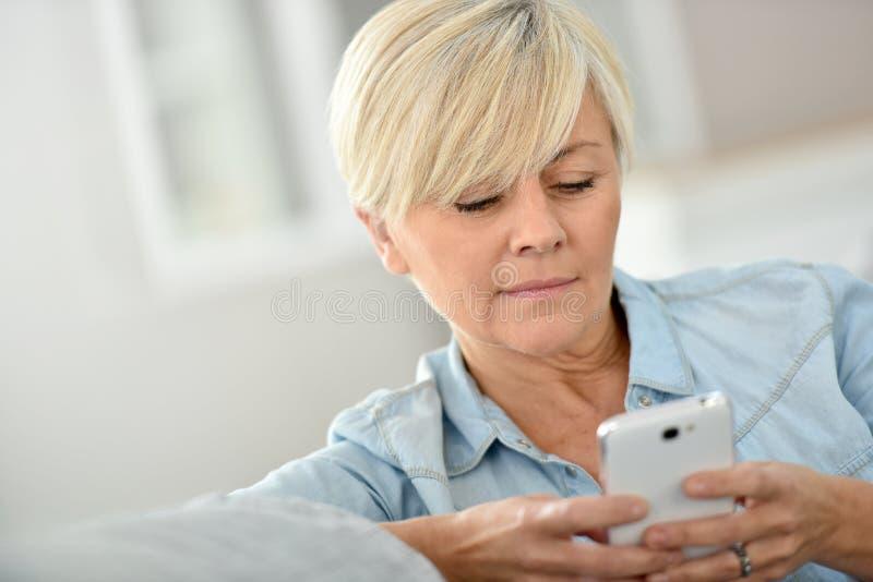 Mujer mayor moderna que manda un SMS con smartphone foto de archivo libre de regalías