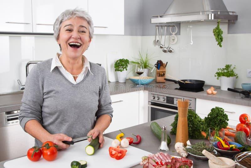 Mujer mayor o más vieja con el pelo gris que cocina en cocina imagen de archivo