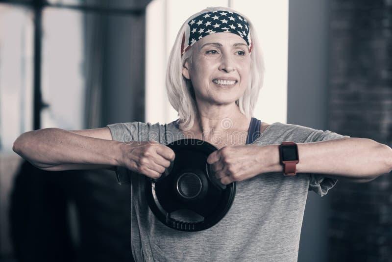 Mujer mayor optimista que sostiene un disco del peso fotos de archivo libres de regalías