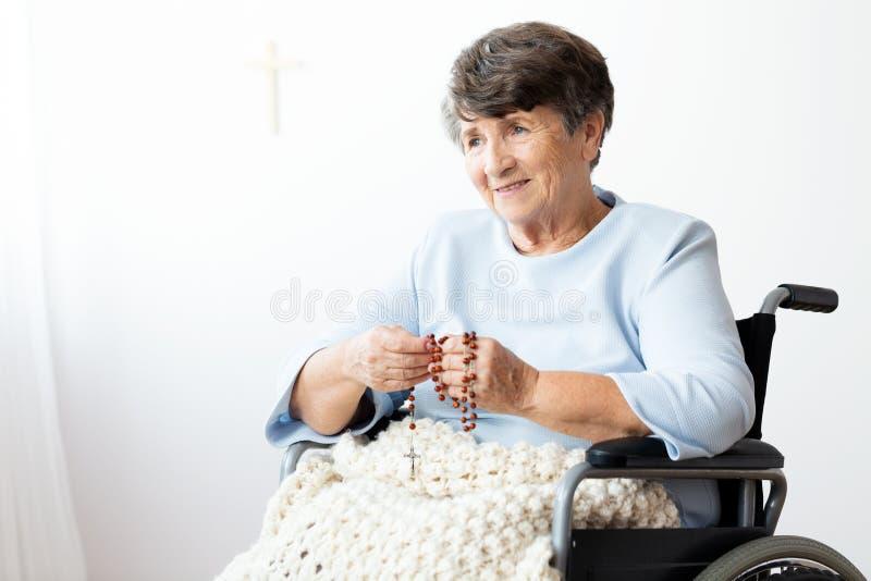 Mujer mayor paralizada en una silla de ruedas que ruega a dios imagenes de archivo