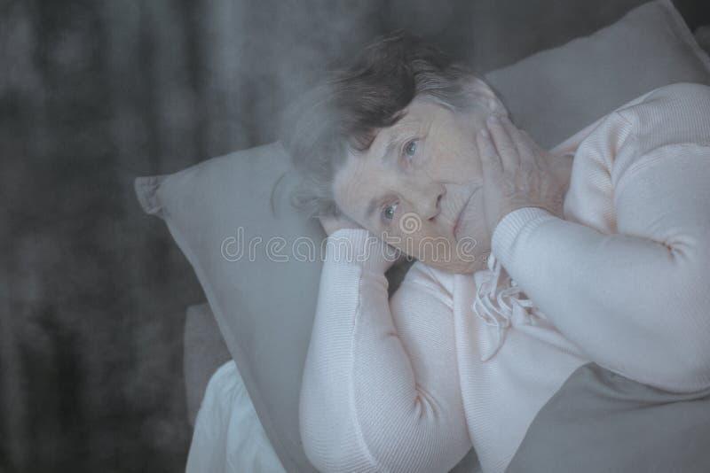 Mujer mayor pensativa en cama imagenes de archivo