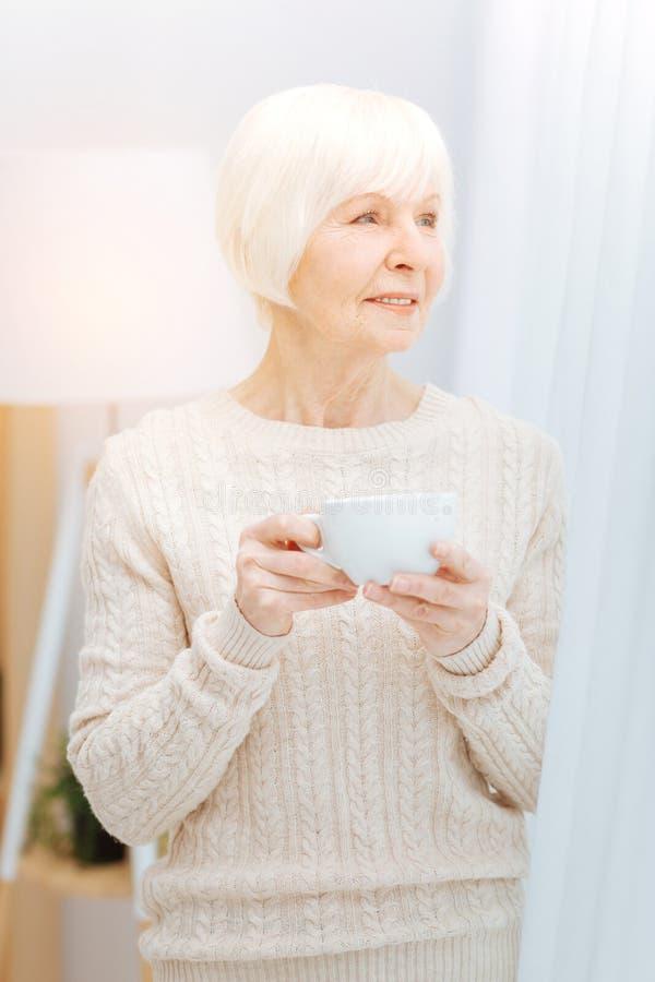 Mujer mayor pensativa que se coloca cerca de la ventana y que sostiene una taza imagen de archivo